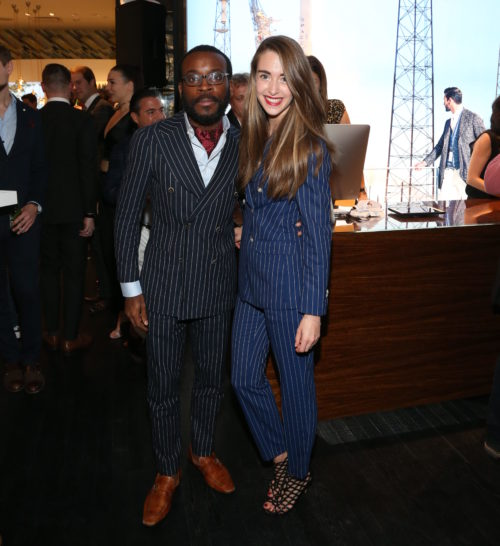 A member of the Suitsupply team right) poses with a guest during the VIP opening. Photo by Gary Miller