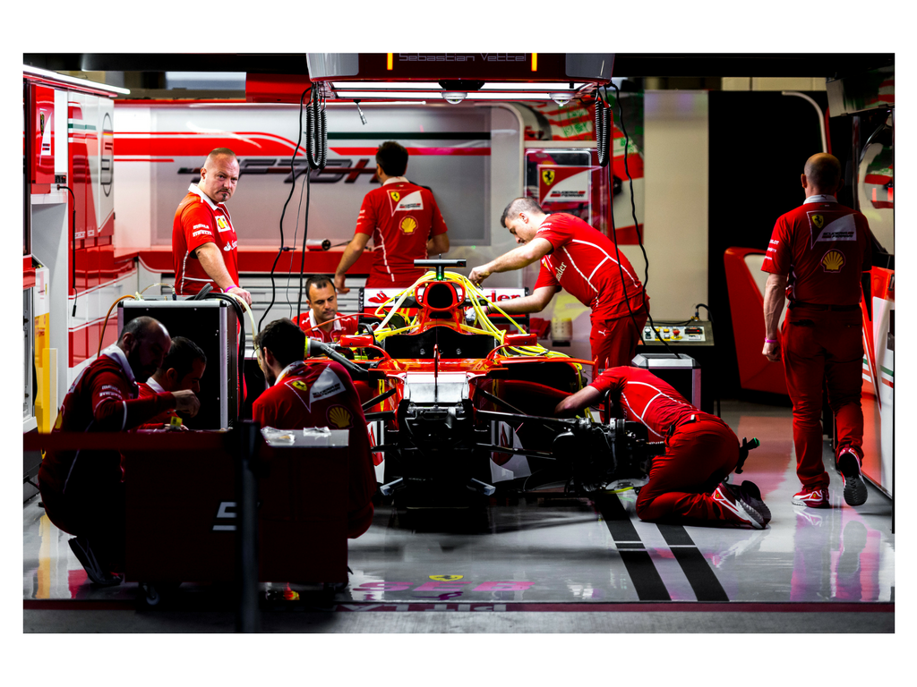 Mechanics prep 2nd-placed Sebastian Vettel's Ferrari before FP1 Friday .